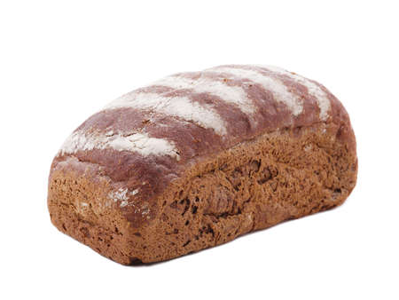 A roll of black bread lies diagonally to the left on a white isolated background. Side view at an angle Stock Photo