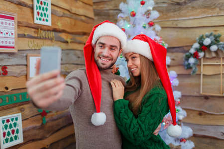 A guy makes a selfie with a girl next to a tree