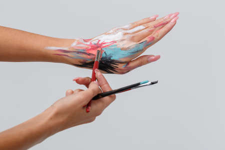 A close-up smeared hand make-up artist in paint, holds a brush, selects the color of the paint. Stock Photo