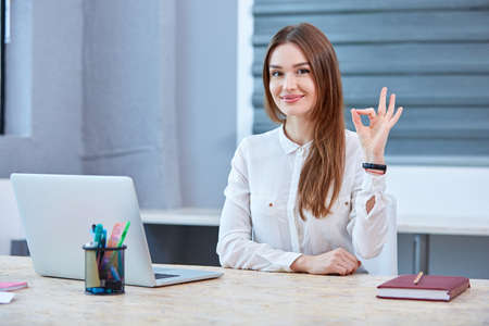 Girl office worker at the table shows a sign that everything is fine
