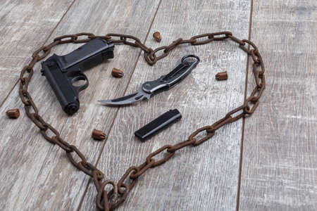 Rusty chain in the shape of a heart in which a gun on a wooden background. Top view from an angle