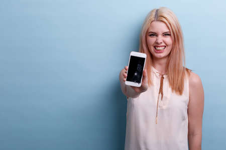 A girl with a wicked smile shows a broken phone on a blue background Stock Photo