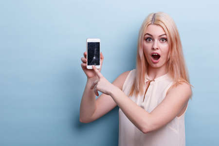 A girl in shock shows at a broken phone and looks directly at a blue background Stock Photo