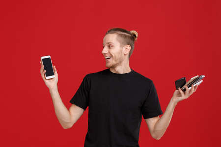 A guy holds a lot of phones in his hands on a red background