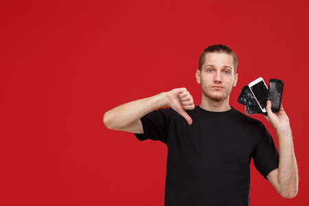 A guy shows his thumb down on a red background