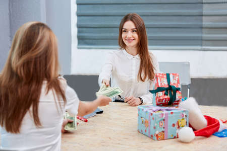The girl transfers money to the office worker Stock Photo