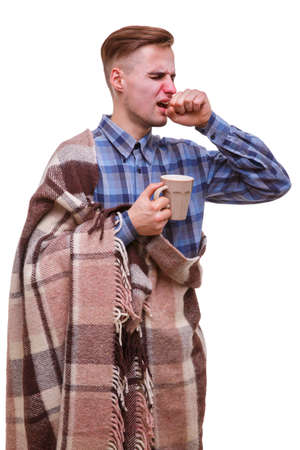 Sick guy sneezes and covers his mouth with his fist on a white isolated background