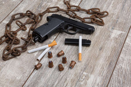 The layout of a pistol, scatteed cartridges, cigarettes, a lighter, a folding knife and an rusty chain. Stock Photo