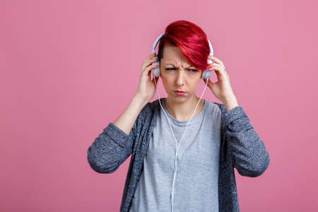 A girl with ear-phones, is grimaces her face from displeasure. Stock Photo