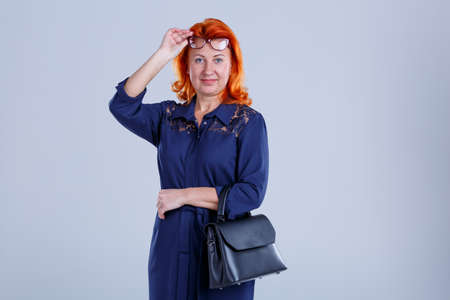 The woman raised her glasses and folded her hands with a bag on a gray background