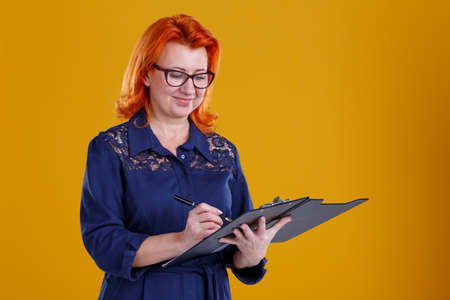 A woman is standing with a tablet making notes and looking at it on a yellow background Imagens