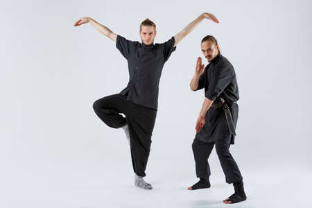 Two ninja pose and crutch on a gray background Stock Photo