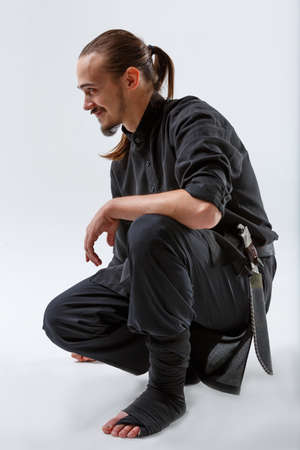 Ninja sat down on one knee close-up on a gray background Stok Fotoğraf - 91352948