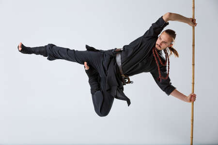 A ninja man holds on to a fighting stick and attacks in a horizontal position with his foot on a gray background