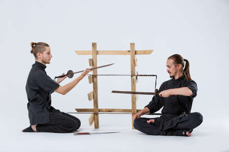 Two ninjas sit on their knees and in a lotus pose they look at swords on a gray background