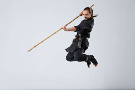 A ninja man attacks in a jump with a fighting stick on a gray background