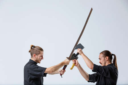 A ninja man blocks a sword with axes of an opponent against a gray background Banque d'images