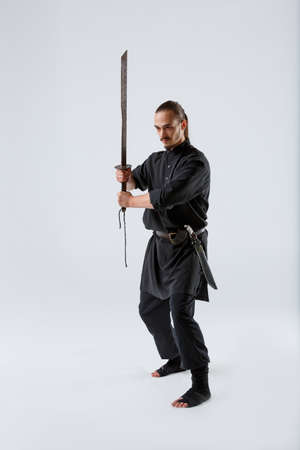 A ninja man concentrates his sword with both hands in front of him against a gray background