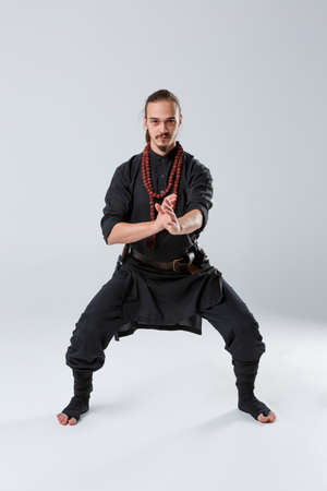 A ninja man stands in a fighting stance against a gray background. Front view Stock Photo