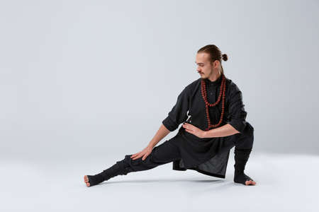 The ninja man crouched and stretched his leg out to stretch the muscles on a gray background