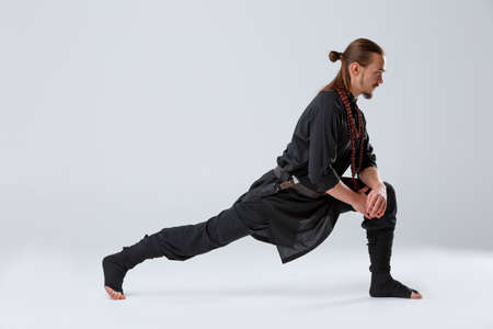 A ninja man pulled his right foot back for stretching muscles against a gray background Stock Photo