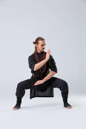El hombre ninja se agachó sobre sus piernas ampliamente espaciadas y puso el bloque sobre sus manos sobre un fondo gris. Vista frontal