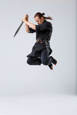 A ninja man in a jump holds the sword with both hands pointing down on a gray background