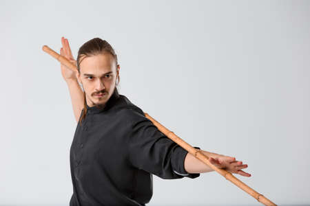 A ninja man stands half-turned with a battle stick behind his neck and holds his hands close-up on a gray background