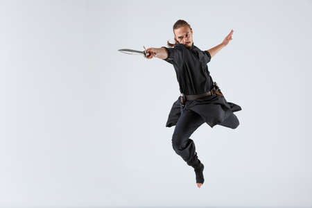 A ninja man jumping with a sword in his outstretched hand against a gray background. Front view