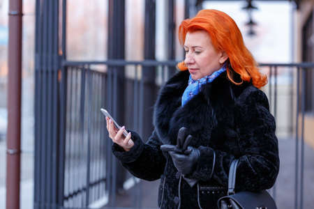 A woman in a fur coat looks at the phone in the street on a blurred background Imagens