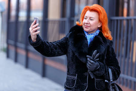 A woman in a fur coat makes selfie on the street in a blurred background Stock Photo