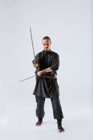 A ninja man holds perpendicular swords in his hands against a gray background