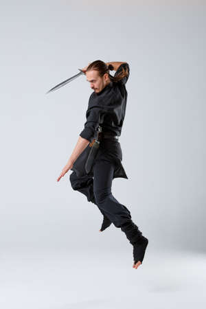 A ninja man jumping and swinging a sword in his hand against a gray background Banco de Imagens - 91353163
