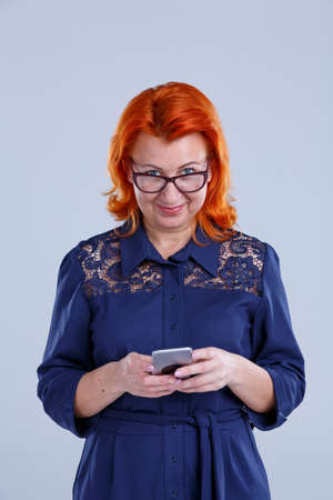 A woman looks directly and dials a message on the phone on a gray background Imagens