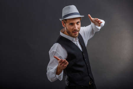 Creative guy in retro suit and hat posing holding hands in front of him at face level.
