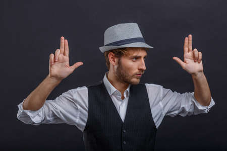 A serious guy in a retro suit and a hat is holding his hands up showing two fingers and looking away.