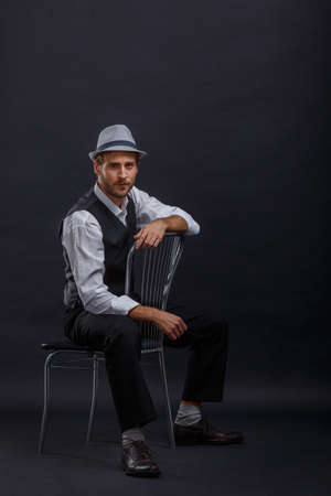 A handsome man in a suit and hat, sitting on chair, legs wide apart. Stok Fotoğraf