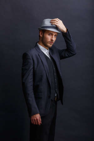 A serious man, in a suit, stands sideways and, with a serious look, adjusts his hat. Stok Fotoğraf