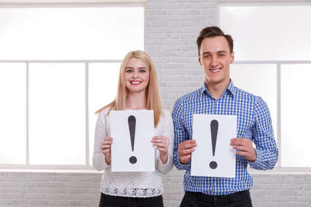 The guy and the girl with a smile are holding the sheets with an exclamation mark Stock Photo