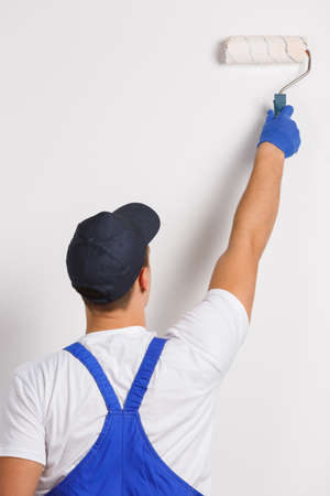 Worker stands with his back and paints a wall close-up on a white background Stock Photo