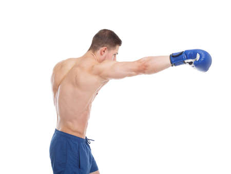 A muscular guy in a boxing glove punches a straight blow against a white isolated background. Side view Stock Photo