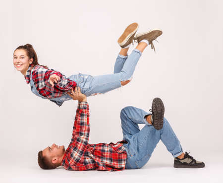 The guy lies and holds the girl above him on a gray background