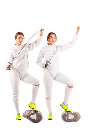 Two girls are fencers, in uniform for fencing and holding swords. Isolated. Stock Photo