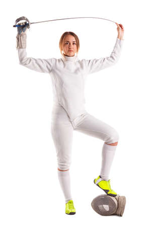 European fencer in form standing, putting one foot on the mask and holding a sword on the raised arms. Isolated. Stock Photo