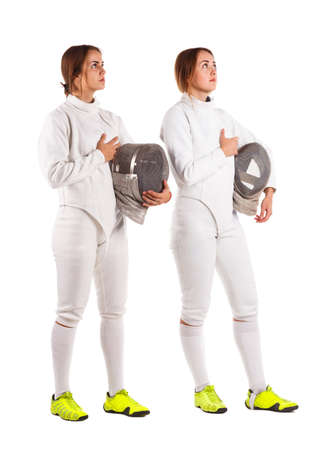 Two girls are fencers, in a uniform, holding a mask for fencing and praying. Isolated on white background.