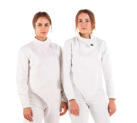 Two European girls are swordsmen, in a fencing uniform posing while standing. Isolated .