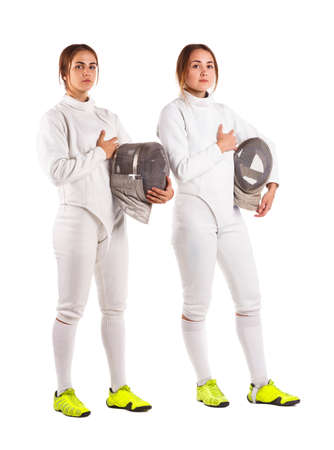 Two girls are fencers, in a uniform, one hand holding a mask and a second hand on the heart. Isolated.