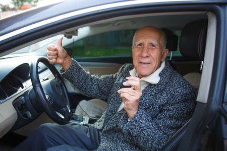 The old man is sitting in the car, holding a small action camera and showing a thumbs-up.