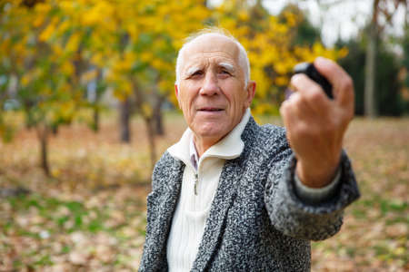 An elderly man, holding a action camera, directing this to himself. Outdoors in the park.
