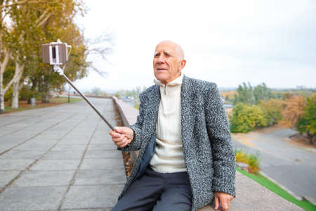 Elderly man makes selfie on a mobile phone with a monopod. Outdoors on the street. Banco de Imagens